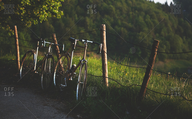 Two bikes lean against a fence