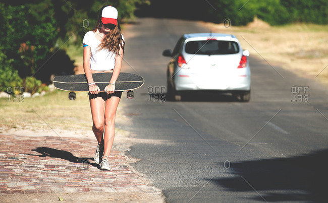 A young woman walks down a road holding a skateboard