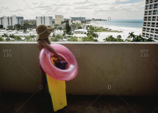 Girl overlooking beach from condo walkway