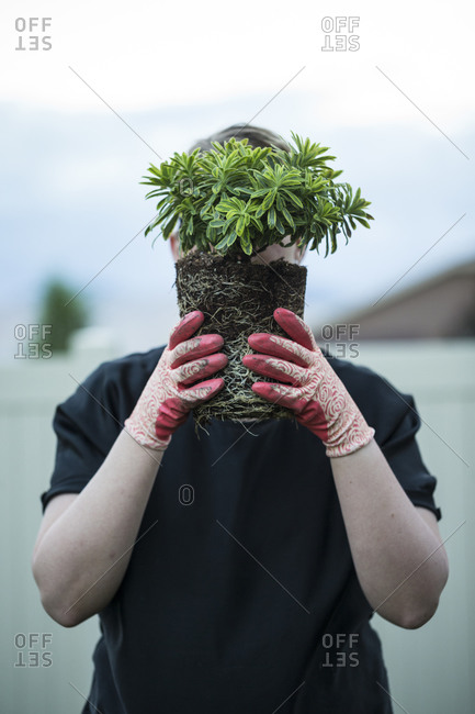 Man in gardening gloves holds a plant in front of his face