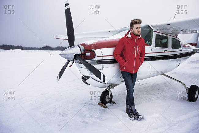 A man stands next to a small propeller plane in the Catskills