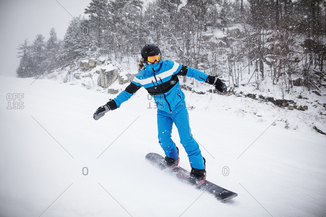 A teen boy rides a snowboard down a mountain in the Catskills