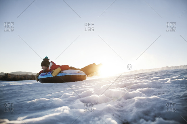 A man goes tubing down a snowy hill in the Catskills