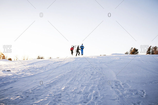 Young men jump up on the top of a snowy hill