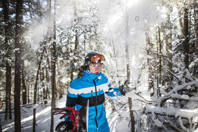 A snowboarder hikes to a trail