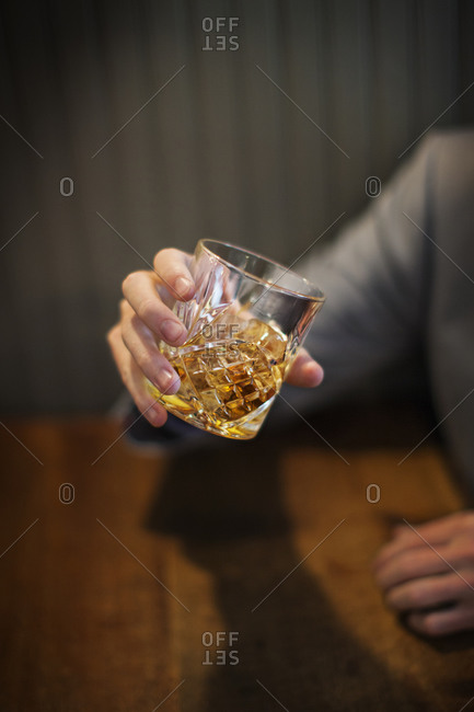 A man holds a glass of whisky