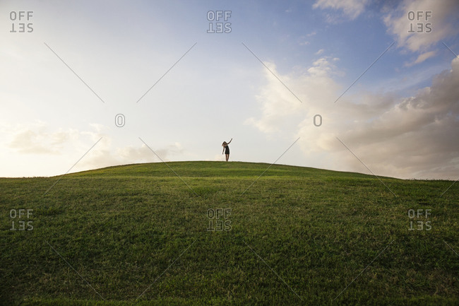 A woman stands at the top of a green hill