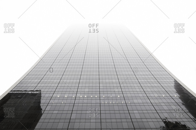 A large glass building rising into the fog