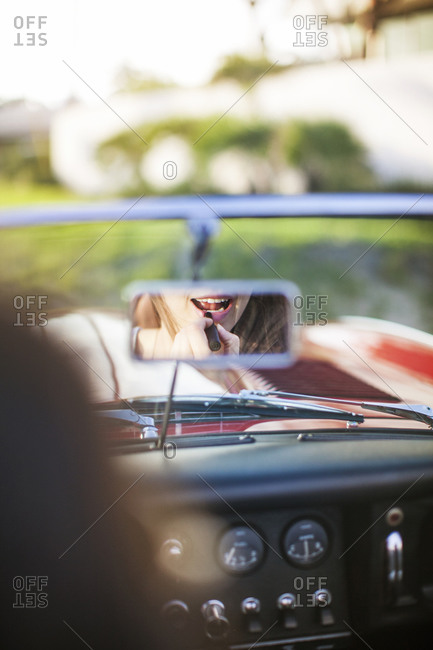 A woman puts on lipstick in her rear view mirror