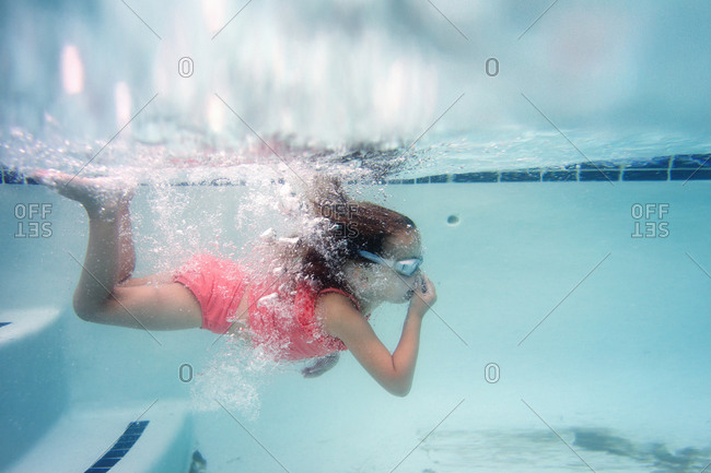 Young girl pinching her nose in a pool