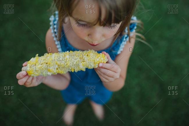 Young girl eating corn on the cob