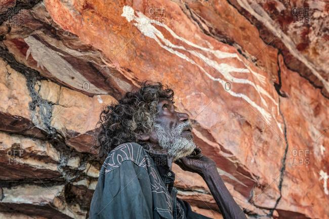 Arnhem Land, Northern Territory, Australia - October 16, 2013: Tom Noytuna, one of the last hunter gathers in Arnhem Land, at a rock art site named Dukaladjarranj