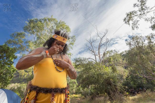 Laura, Queensland, Australia - June 22, 2013: Woman applying tribal body paint on herself at the Laura Aboriginal Dance Festival