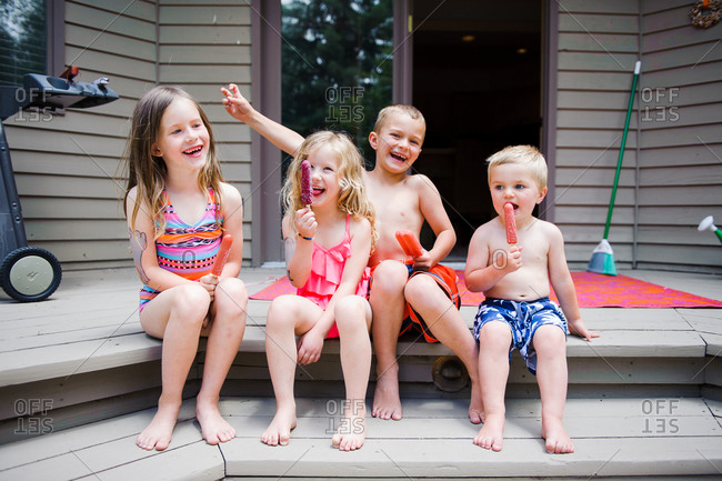 Four young children enjoying popsicles on deck