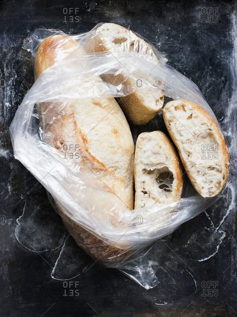 Fresh loaf and sliced bread in a plastic bag on stone surface