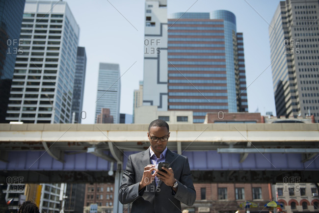 Businessman holding phone outdoors in city