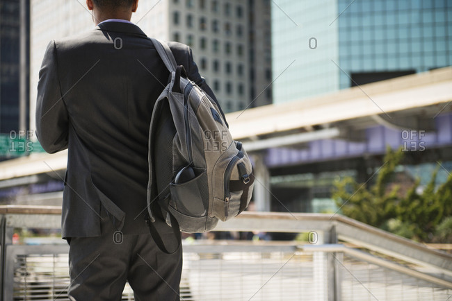 Man in suit with backpack outdoors in city