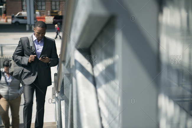 Man in suit walking in city with phone