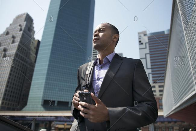 Businessman holding phone thinking