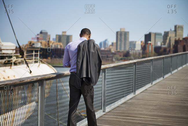 Man in suit walking on city pier