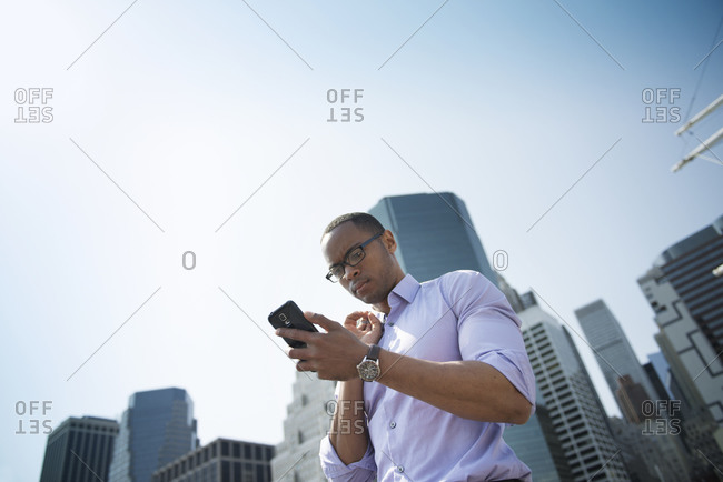 Businessman in city checking phone