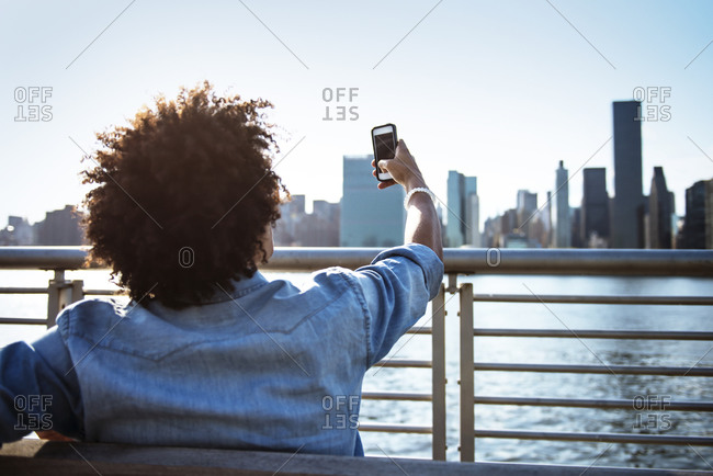 Young man taking picture of city with phone
