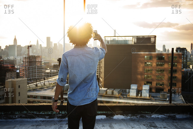 Man on roof at sunset taking picture