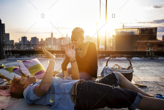 Couple lounging on rooftop at sunset