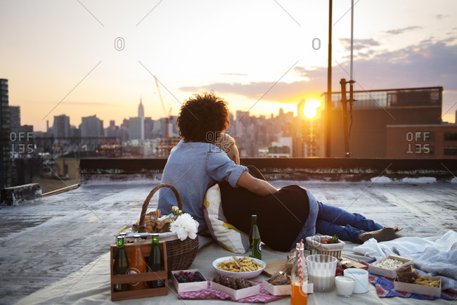 Couple sitting together during rooftop picnic