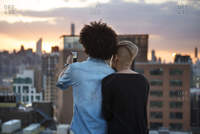 Couple with phone on city roof