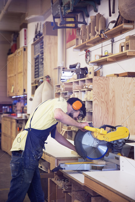 Man cutting with buzz saw in workshop