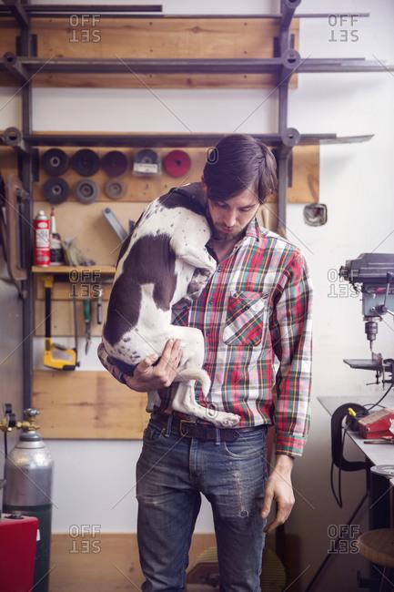 Carpenter holding dog in workshop