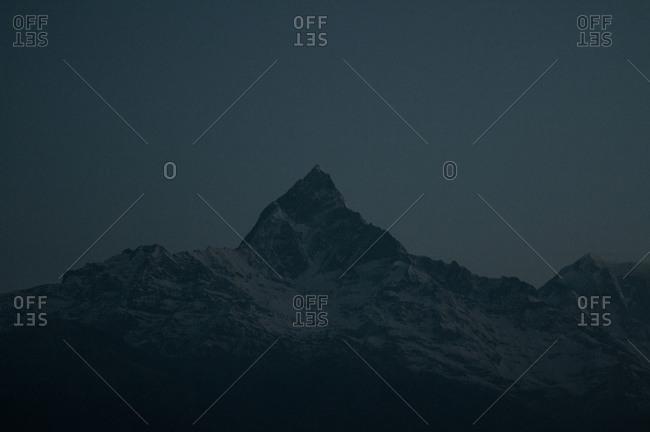 A steep mountain peak under a dark sky