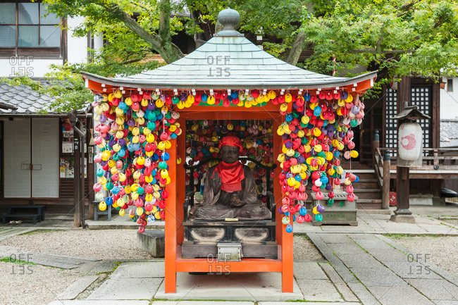 Buddhist statute with spools of thread