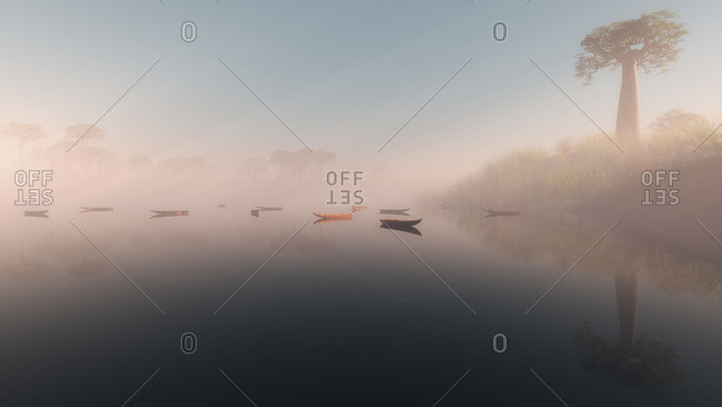 Tranquil lake with moored boats in the mist at sunrise