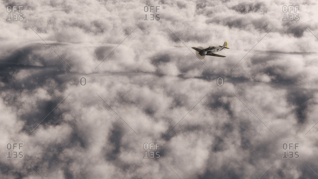 Small private single-engine plane flying over clouds in the stratosphere