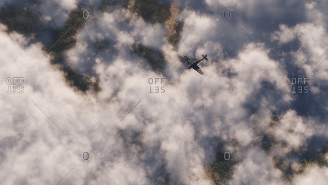 Aerial view of a black propeller airplane flying above scattered cloud cover