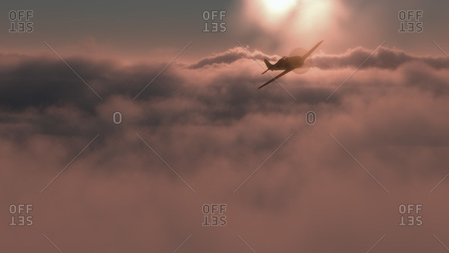 Small plane flying above pink clouds at sunset with the bright fiery orb of the sun in the background
