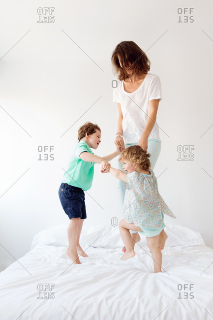 A mother and her children jump on a bed