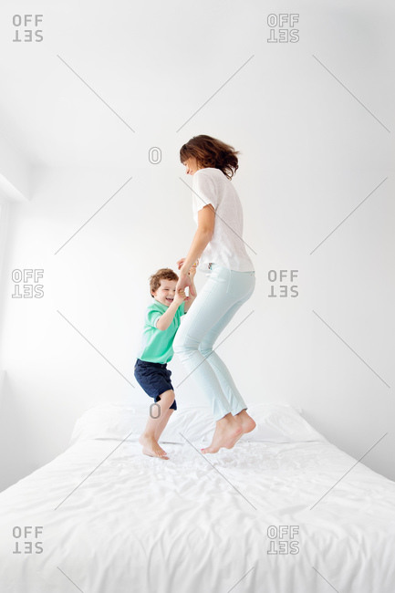 A mother and son jump on a bed