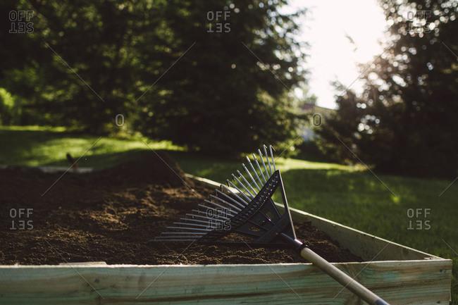 A rake left on a raised garden bed