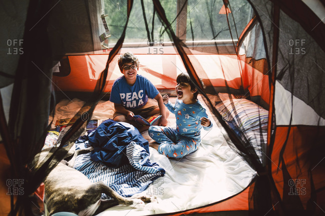 Two brothers play in a tent indoors