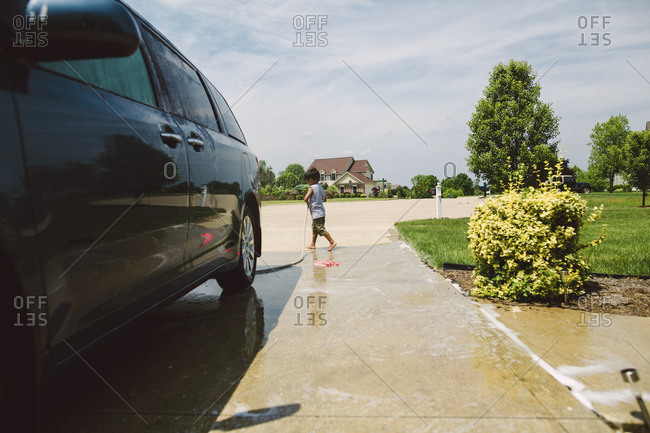 A little boy washes his car in his driveway