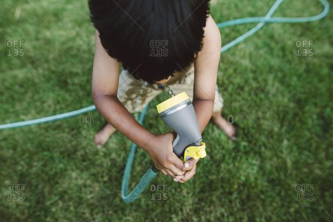 A little boy drinks water from a garden hose