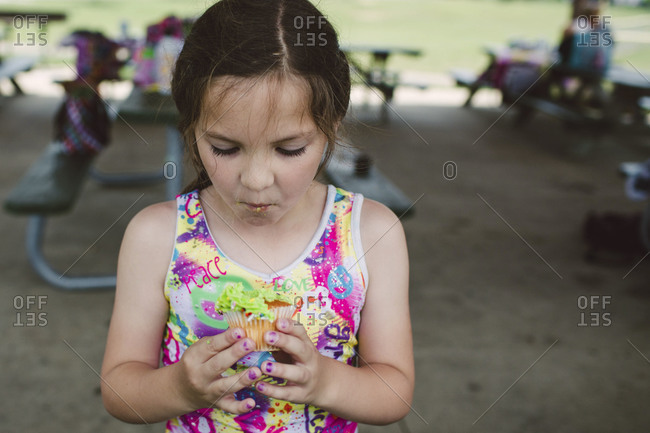 A little girl eats a cupcake at her birthday party