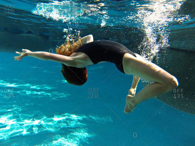 A little girl does a backflip under water