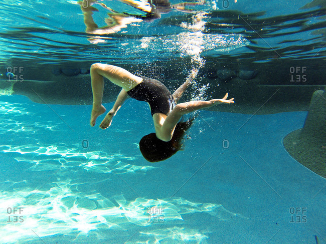 A girl does a somersault underwater
