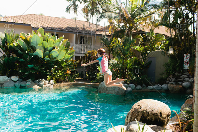 A girl jumps off of a rock into a pool