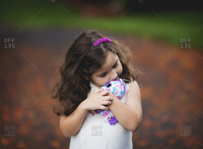 A little girl cuddles with her stuffed animal outside