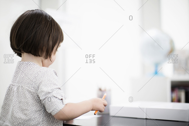 Young girl with pencil at a desk in room with modern decor